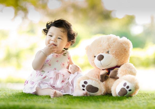 dítě sedící na trávě s plyšovým medvědem